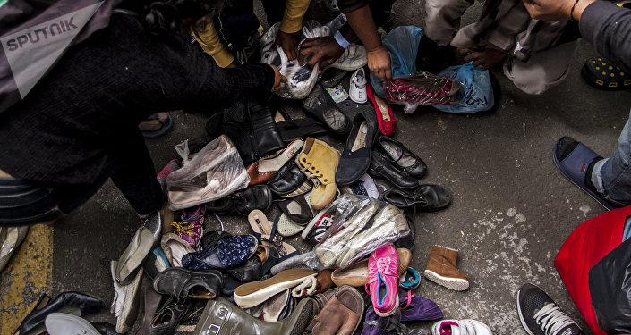 Integrantes de la segunda caravana del éxodo centroamericano buscan zapatos en buen estado que puedan utilizar