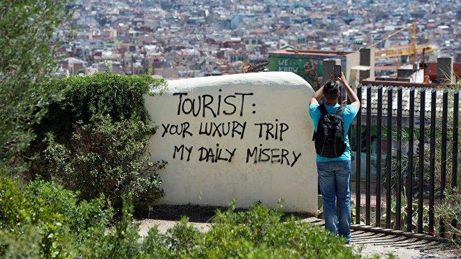 Vista a la ciudad de Barcelona desde el Park Guell, con una inscripción 'Turista: tu viaje de lujo es mi miseria diaria'