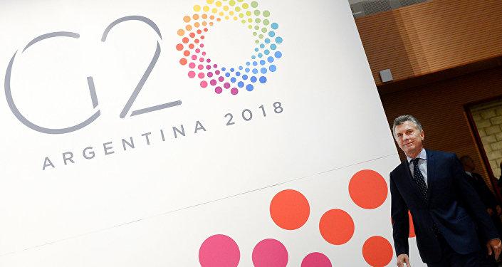 Mauricio Macri junto a un cartel del G20
