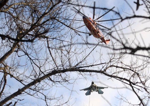 Un helicóptero Mi-26 transporta a un caza Su-27
