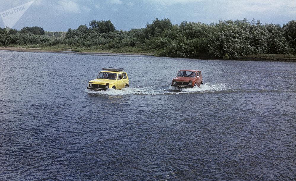 Dos vehículos Lada Niva cruzan un río en Siberia, 1977