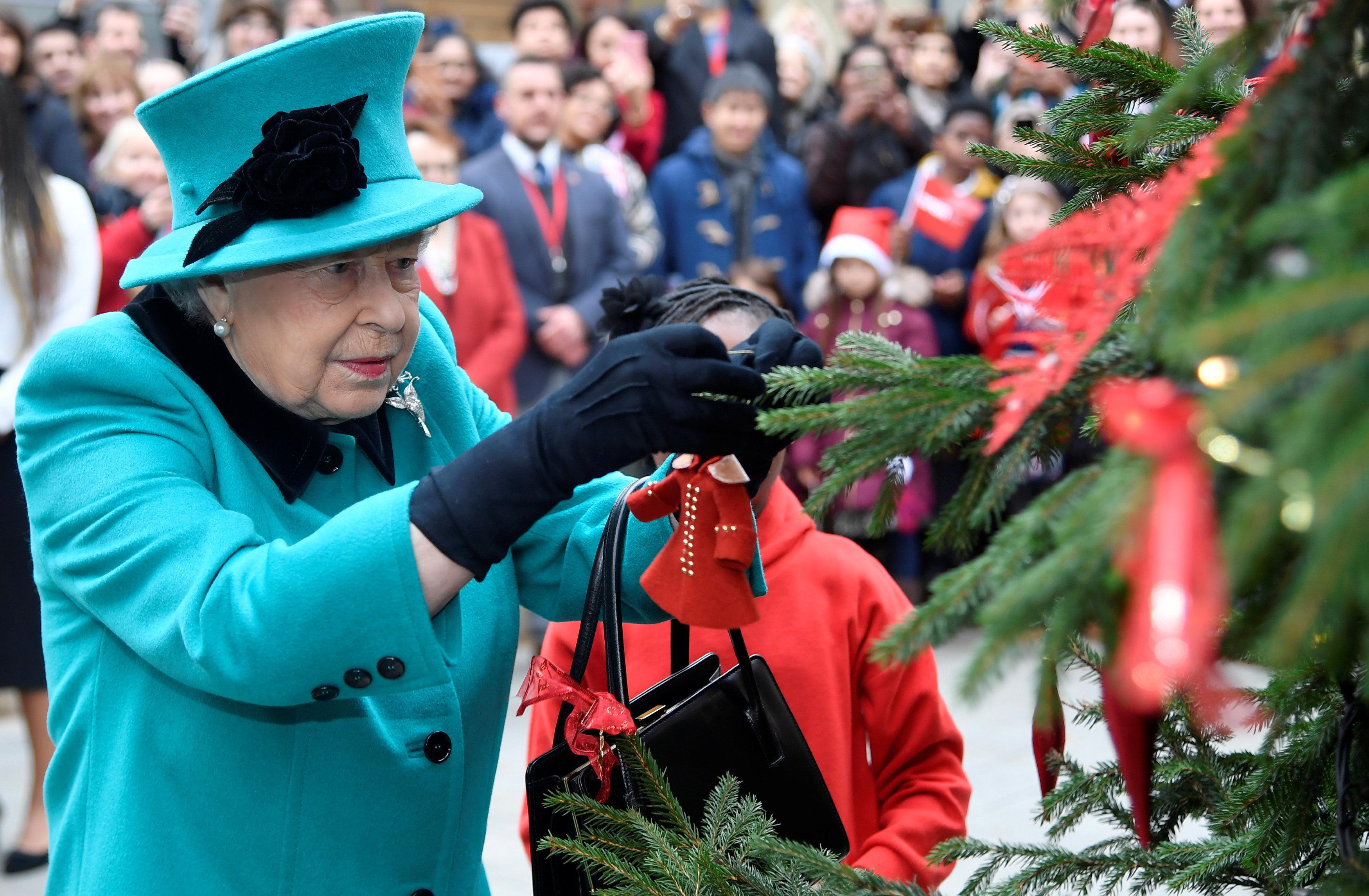 La reina Isabel II, de Reino Unido, coloca un chirimbolo en el árbol de Navidad de la organización benéfica infantil Coram, en Londres
