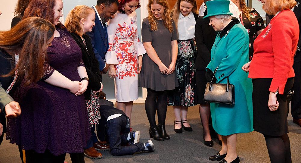 Un niño se arrastra mientras la reina británica Isabel visita la organización benéfica infantil Coram en Londres