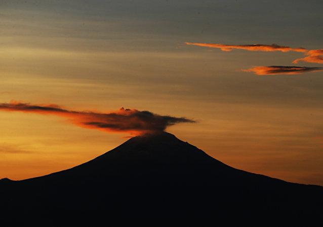 Una columna de ceniza y vapor se eleva desde un volcán