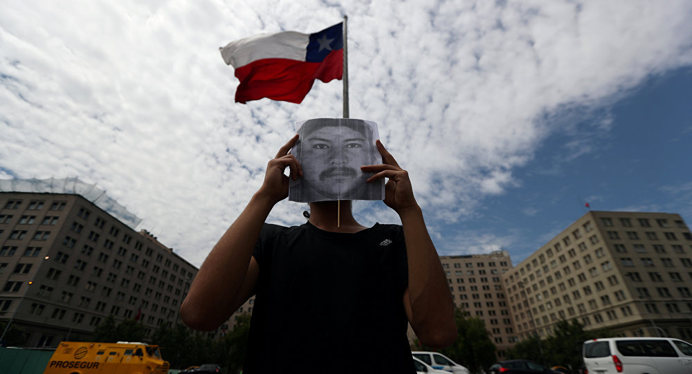 Un manifestante con el retrato del comunero mapuche Camilo Catrillanca