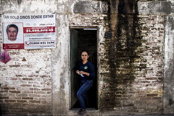 Mayra Vergara sale de su oficina, en Huitzuco, Guerrero, donde se ve el cartel que anuncia la búsqueda de su hermano Tomas Vergara, desaparecido el 5 de julio de 2012