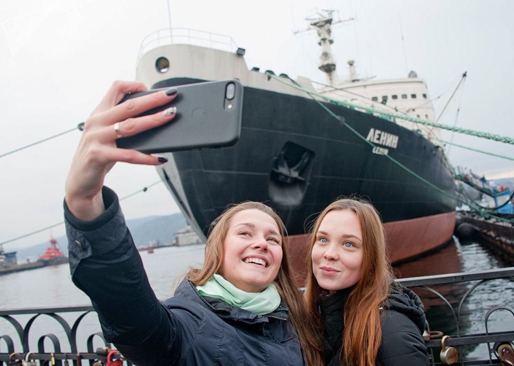 Dos muchachas sacándose una foto al lado del rompehielos Lenin