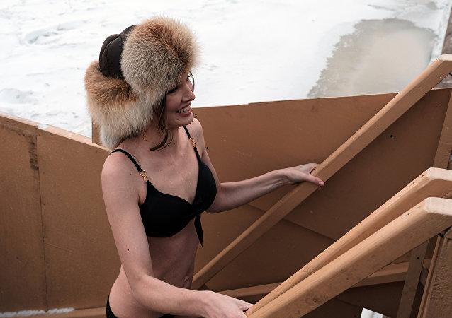 Una mujer preparándose para darse un baño al aire libre en invierno en Rusia