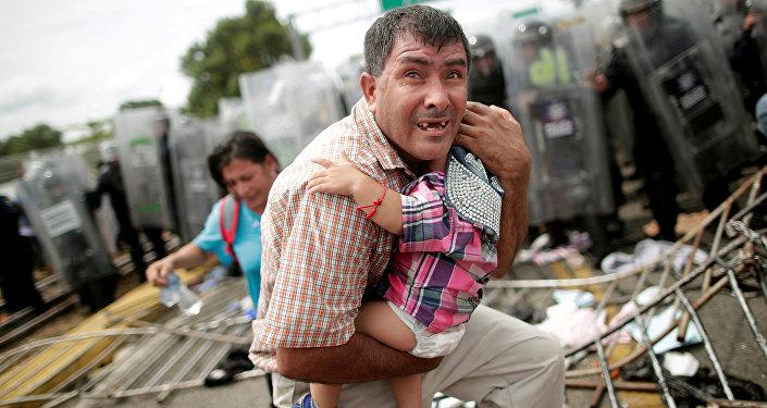 Un migrante trata desesperadamente de proteger a su bebé durante un choque en el cruce de la frontera entre México y Guatemala, el 19 de octubre de 2018