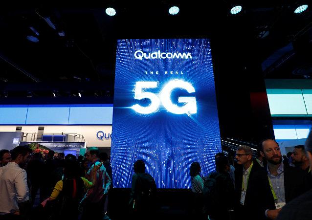 La gente pasa al lado de una pantalla que promociona la conectividad 5G en el stand de Qualcomm