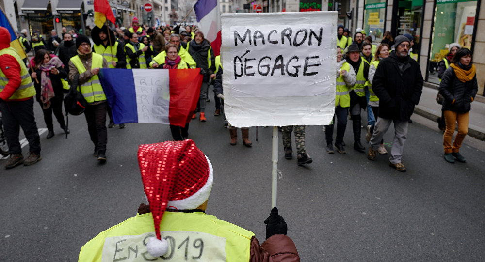 Los 'chalecos amarillos' protestan con el cartel 'Macron, largate!' en París