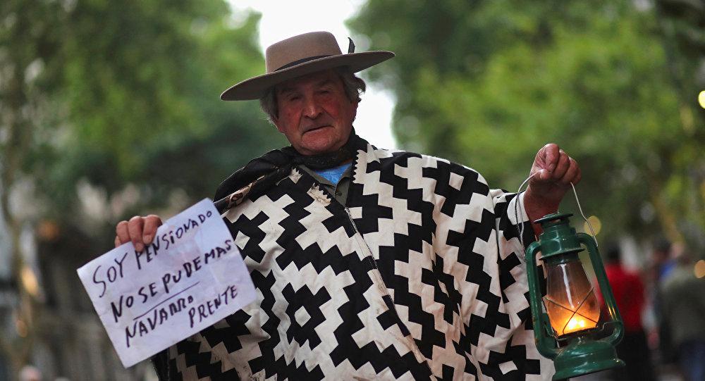 Un hombre sostiene una linterna en una marcha de protesta contra el incremento de tarifas en Buenos Aires