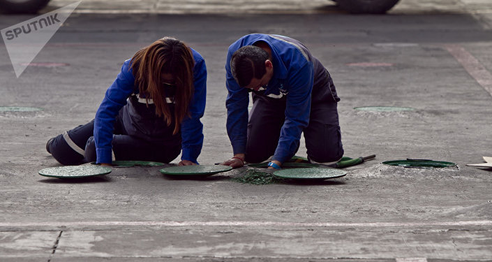 """Trabajadores de una gasolinera limpian las tomas de relleno durante el desabasto de su local debido a las """"compras de pánico"""" según el gerente, Abel Luna"""