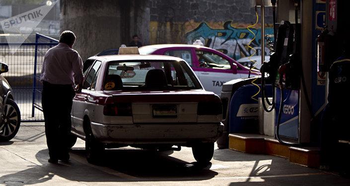 Taxista al terminar de llenar su tanque de gasolina. La mayoría de las filas están llena de taxistas