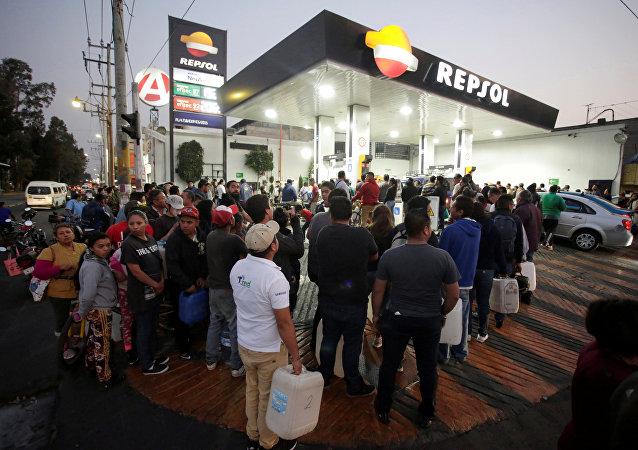 Mexicanos hacen cola en una gasolinera, en Ciudad de México