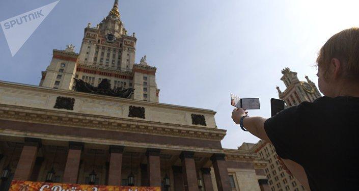 Una estudiante toma una foto de su identificación en la Universidad Lomonósov de Moscú