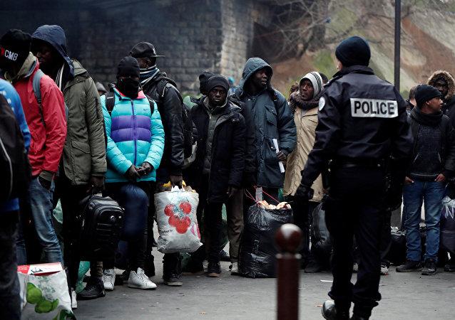 La Policía francesa evacua un campamento de migrantes La Chapelle en el norte de París, Francia