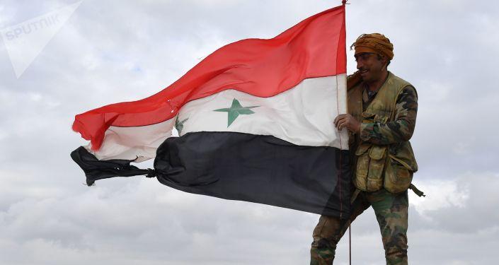 Un soldado sirio izó la bandera nacional (archivo)