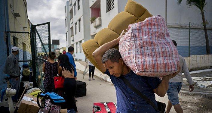 Un hombre carga sus pertenencias a un bus en La Habana después del tornado del 27 de enero