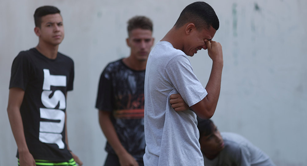 Un jóven llora tras el incendio en un club de fútbol en Río de Janeiro