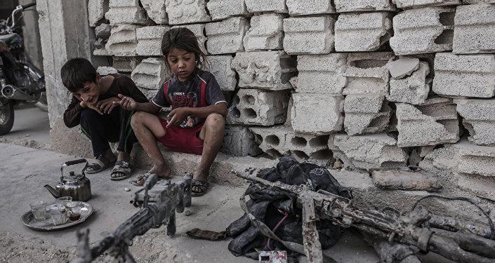 Niños miran en armas incautadas a los terroristas de ISIS en Irak