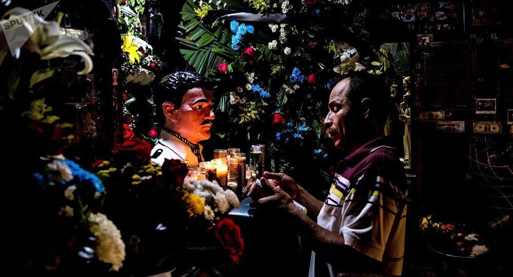 Culiacán, Sinaloa. Hombre reza frente a la imagen de Jesús Malverde en su capilla.