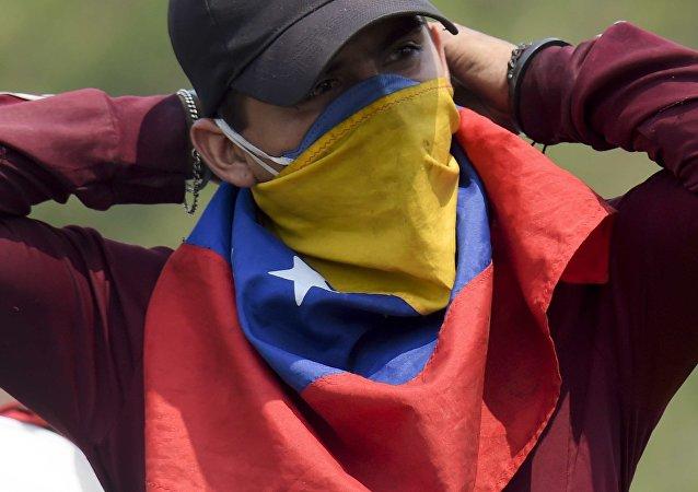 Un manifestante con la bandera de Venezuela en su cara