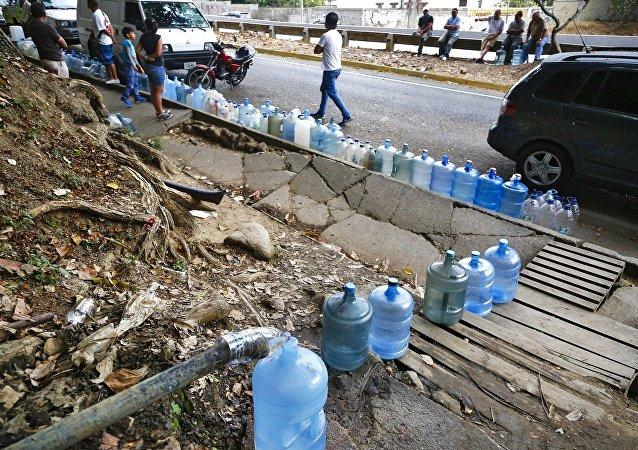 Venezolanos rellenan botellas de agua durante apagón en Caracas (archivo)