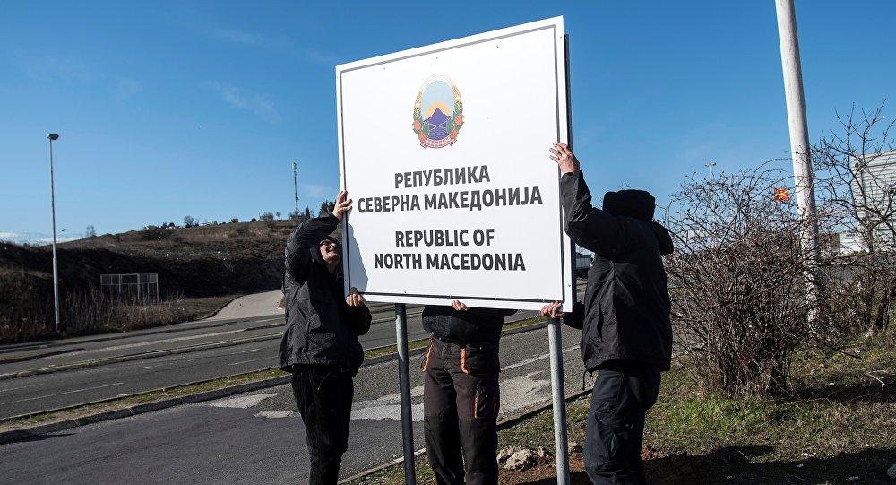 Obreros cambian carteles en un puesto de control fronterizo en Macedonia del Norte