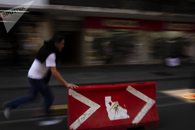 Mauro toma señalamientos de tránsito para cortar el tráfico durante la marcha contra la reubicación del mercado Santa Cruz Meyehualco.