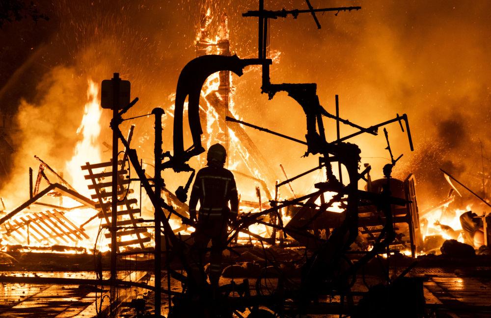 Así apagan el fuego de los ninots quemados en plenas fallas de Valencia (España)