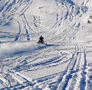 Sale volando por los aires a bordo de una moto de nieve a toda velocidad