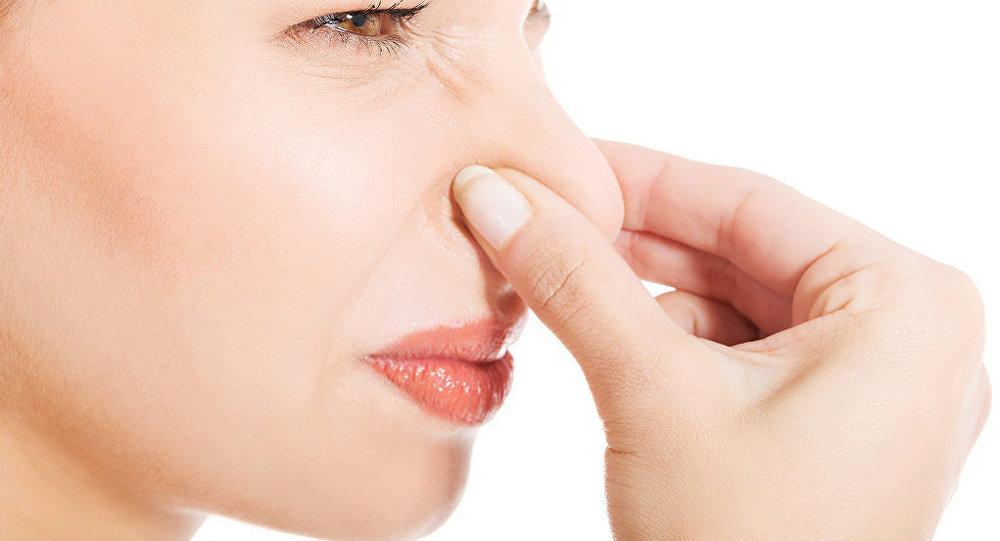 Mujer se tapa la nariz por el olor.