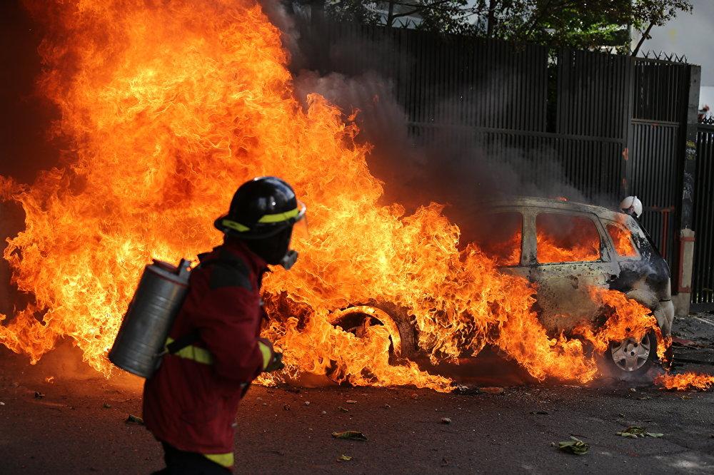 Un bombero apaga el fuego de un carro en llamas durante las protestas en Caracas