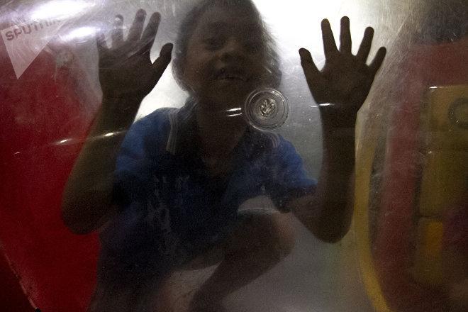 """Niño de la caravana migrante juega en el """"Teatro del Pueblo"""" de Huehuetán, Chiapas, México"""