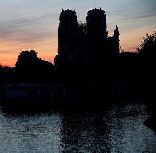 Las torres de la catedral de Notre-Dame se reflejan en el río Sena al atardecer