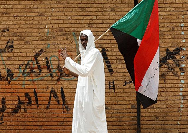 Un hombre con la bandera de Sudán