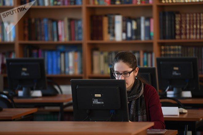 Una chica usa un ordenador en una biblioteca