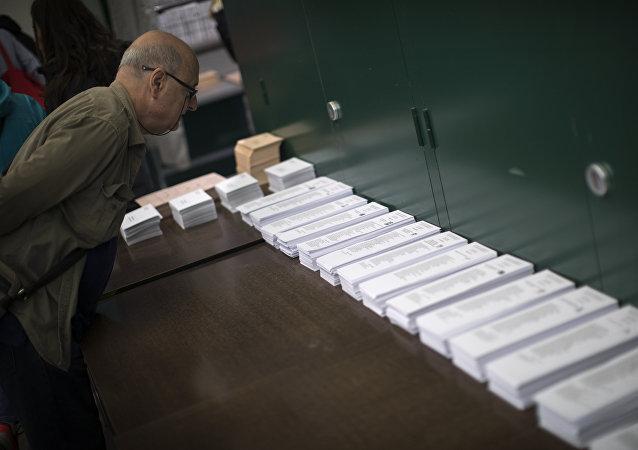 Un hombre inspeciona las papeletas en una mesa electoral en Barcelona