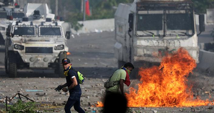 Seguidores de la oposición venezolana caminan en frente de un vehículo militar durante un enfrentamiento con las fuerzas de seguridad