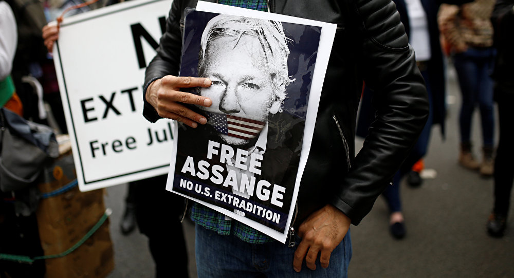 Una persona con un retrato de Julian Assange