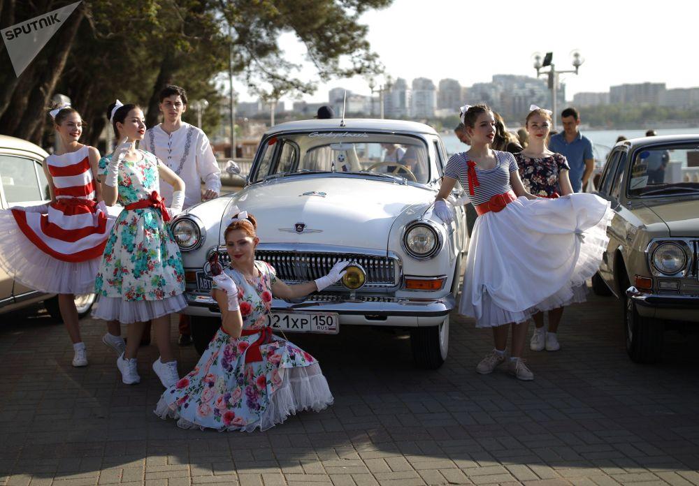 Unas jóvenes se toman fotos cerca del coche GAZ-21 Volga en Gelendzhik.