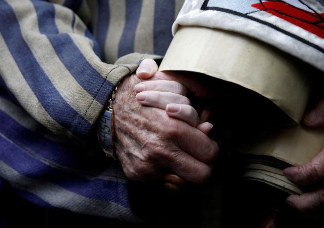 Sobreviviente del holocausto toma la mano de su hija