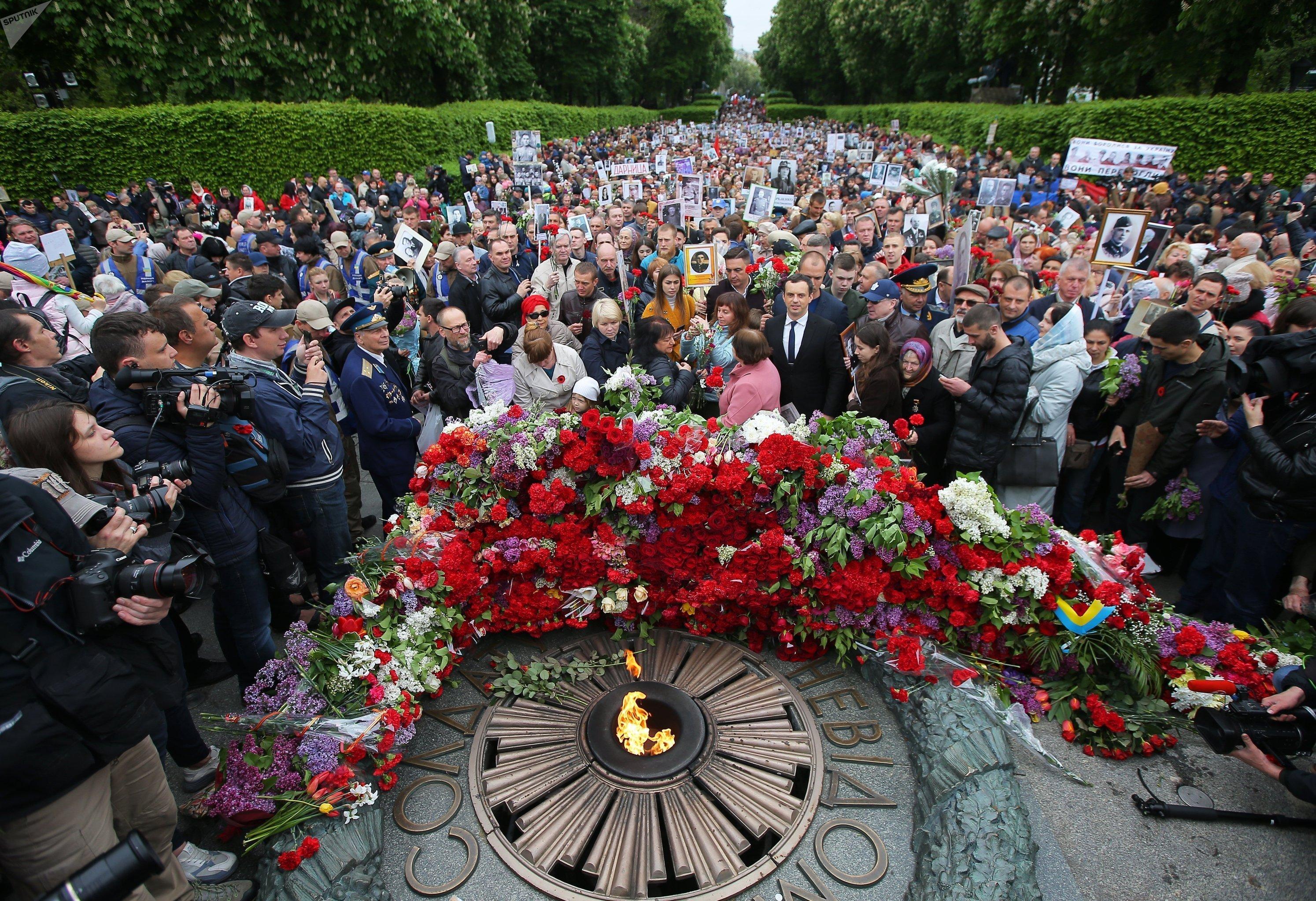 El Regimiento Inmortal deja flores en el fuego eterno del parque de la Victoria en Kiev