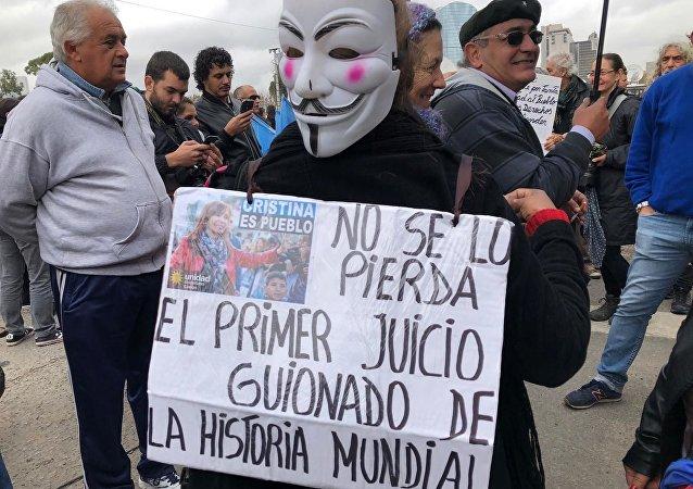 Una mujer con un carten en apoyo a Cristina Fernández fuera de tribunales