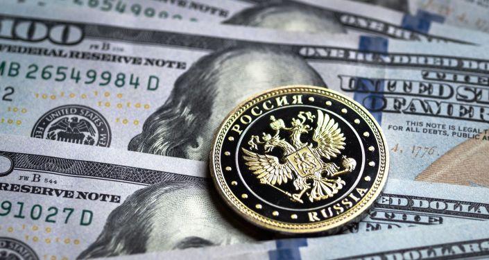 Billetes de dólares y una moneda del rublo