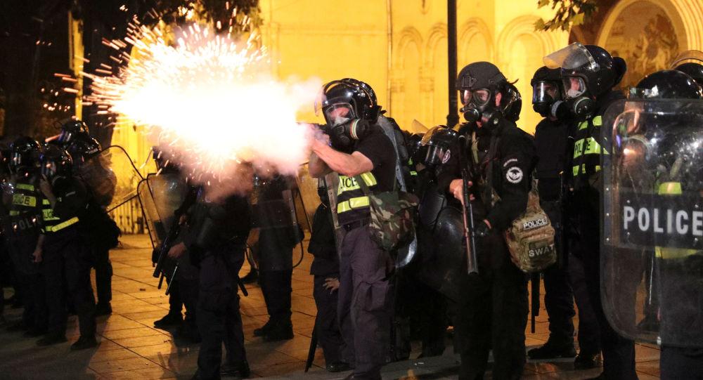Un policía dispara durante las protestas en Tiflis, Georgia