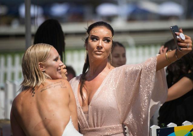 Las mujeres hacen una selfi antes del comienzo de las carreras Met horse race en Ciudad del Cabo, Sudáfrica