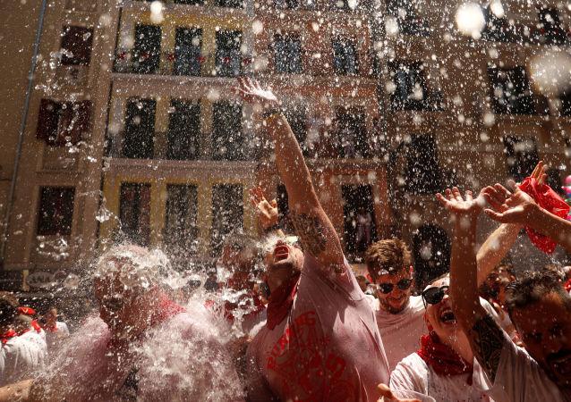 La gente se refresca con agua lanzada desde un balcón durante la inauguración del festival de San Fermín en Pamplona (España)