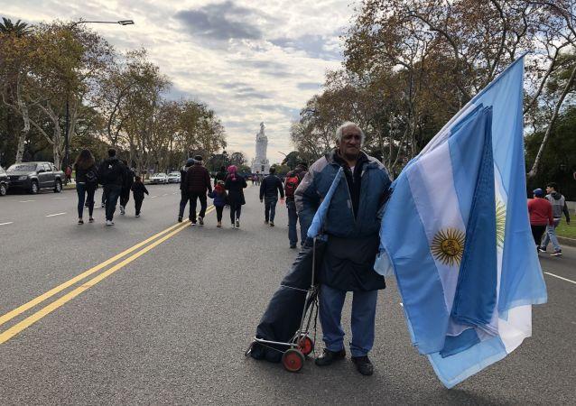 Un hombre vende banderas en la Avenida Libertador en el Día de la Independencia de Argentina